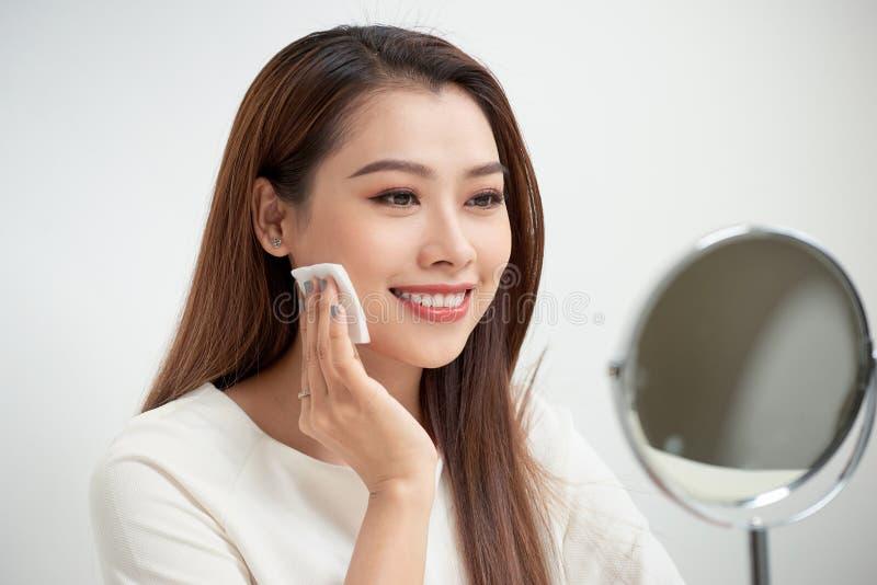 离开她的构成 使用棉花盘的美丽的快乐的年轻女人和看她的反射在有微笑一会儿的镜子 免版税库存图片