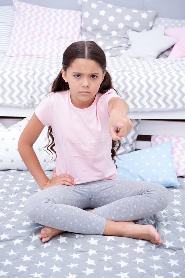 离开我的室 女孩孩子坐床在她的卧室 哄骗不快乐进入了她的卧室打扰她的某人 女孩 库存照片