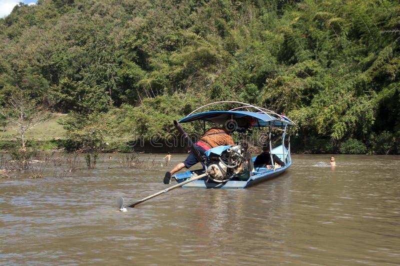 离开村庄的帆船附载的大艇,当孩子是在水中时 免版税库存照片