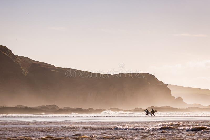 离开海洋的冲浪者在大风天 免版税库存图片