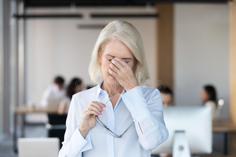 离开玻璃的疲乏的被疲劳的资深女性雇员感觉累眼 库存照片