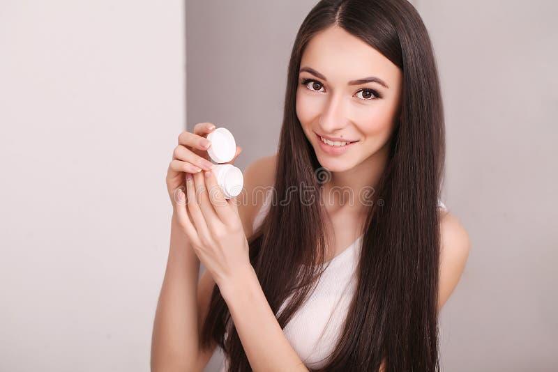 秀丽、人、化妆用品、skincare和健康概念-应用奶油的愉快的微笑的少妇于她的面孔 免版税图库摄影
