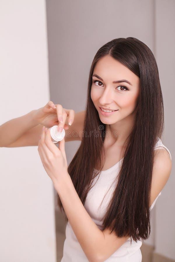 秀丽、人、化妆用品、skincare和健康概念-应用奶油的愉快的微笑的少妇于她的面孔 免版税库存照片
