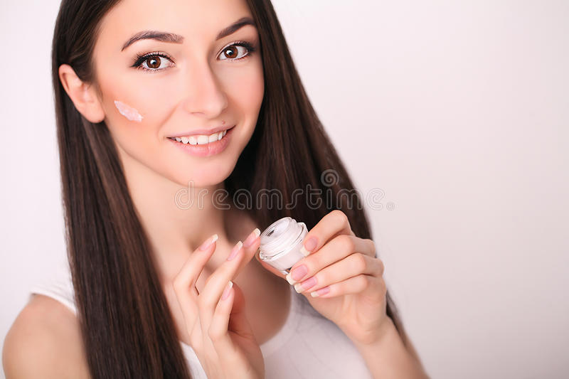 秀丽、人、化妆用品、skincare和健康概念-应用奶油的愉快的微笑的少妇于她的面孔 库存照片