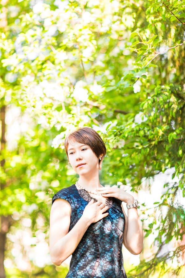 秀丽、人们、夏天和春天概念-在绿色开花的庭院背景的美丽的少妇 库存图片