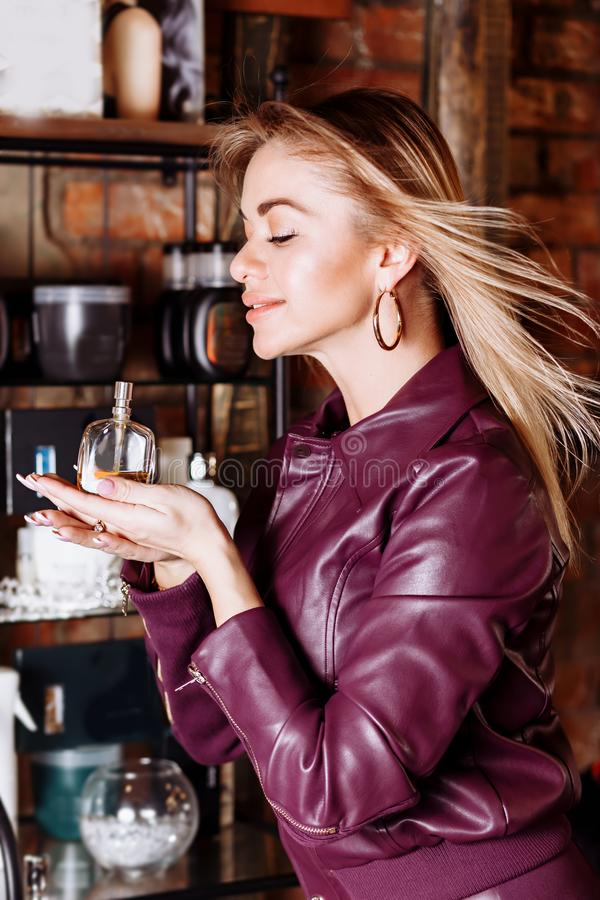 秀丽、芳香、人和身体关心概念 有白肤金发的飞行的头发佩带的紫罗兰色皮夹克藏品的年轻可爱的妇女 库存照片
