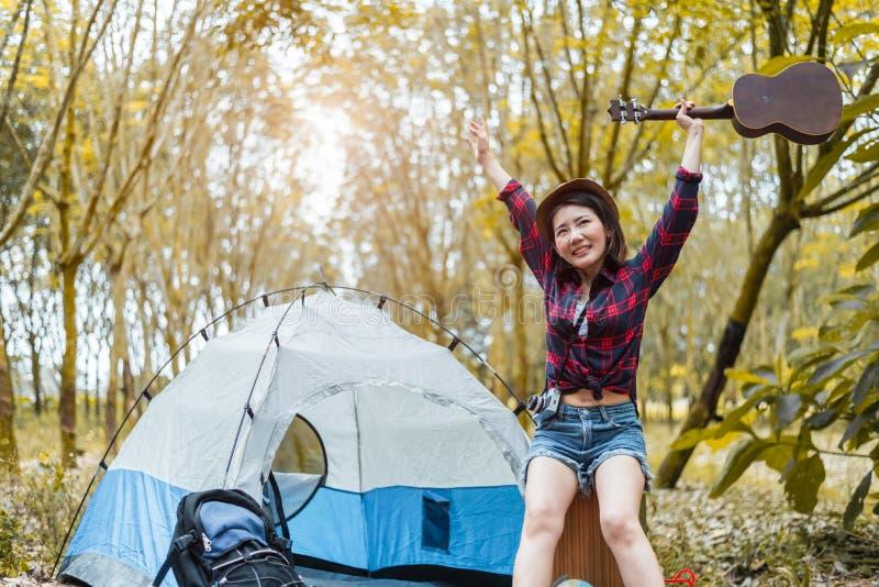 秀丽亚洲妇女藏品吉他和上升手在森林松木背景中 人们和生活方式concet 野营和 图库摄影