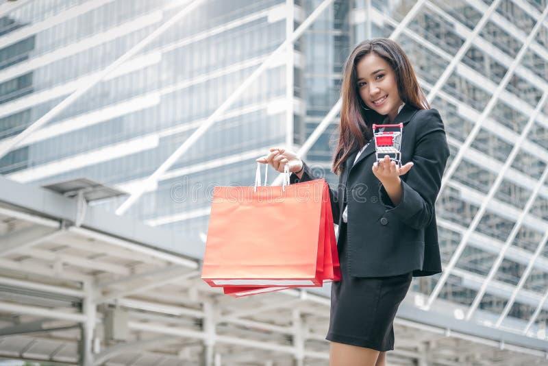 秀丽亚洲妇女藏品购物带来和手推车在购物中心 在黑星期五和网络星期一销售概念的Shopaholic 公共汽车 库存照片