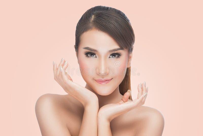 秀丽亚洲画象,接触她的面孔的美丽的温泉妇女 完善的新鲜的皮肤 免版税库存照片