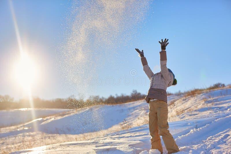 秀丽冬天女孩吹的雪在冷淡的冬天公园 户外 飞行雪花 晴朗的日 由后照 秀丽年轻人 免版税库存照片