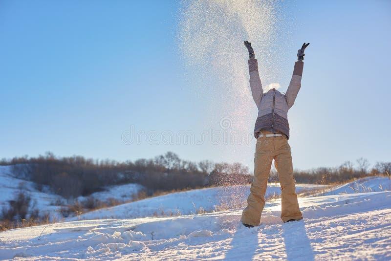 秀丽冬天女孩吹的雪在冷淡的冬天公园 户外 飞行雪花 晴朗的日 由后照 秀丽年轻人 免版税库存图片