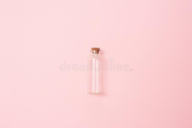 秀丽化妆用品glassbottle;烙记的假装;在粉红彩笔背景的顶视图 精油的包裹 库存图片