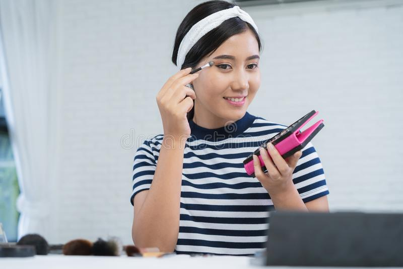 秀丽博客作者礼物秀丽化妆用品,当坐在记录的录影的时前面照相机 美丽的妇女用途刷子 库存照片