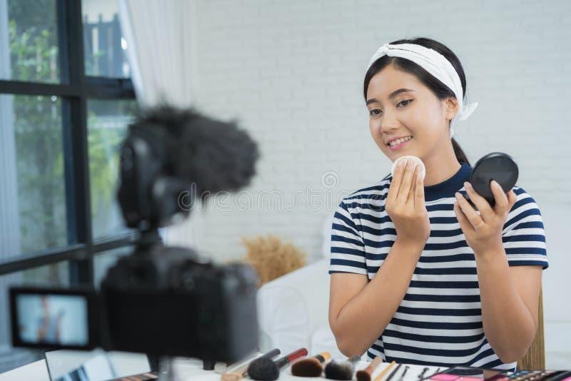 秀丽博客作者礼物秀丽化妆用品,当坐在记录的录影的时前面照相机 美丽的妇女用途粉末 免版税库存照片