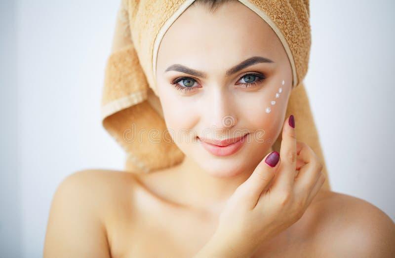 秀丽和关心 一个女孩的画象有布朗毛巾的在头 有纯净的皮肤的少妇 举行在手上提取乳脂 E 免版税图库摄影