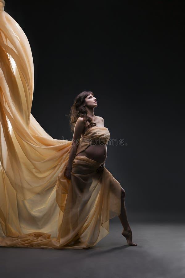 年轻秀丽和性感的白种人孕妇有黄色丝绸的在灰色演播室背景 图库摄影