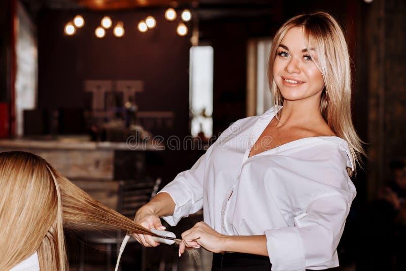 秀丽和护发概念 美丽的快乐的白肤金发的做对她女朋友头发称呼的妇女佩带的白色衬衫 库存图片