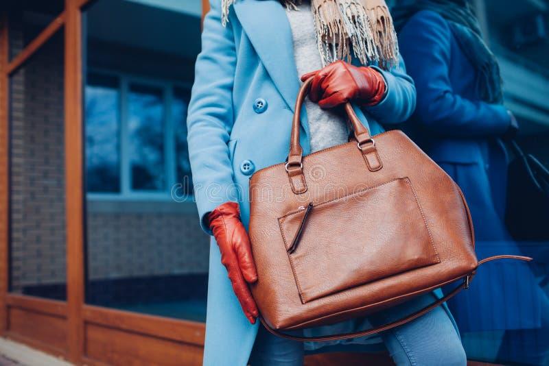 秀丽和方式 时髦的时髦的女人佩带的外套和手套,拿着棕色袋子提包 免版税库存图片