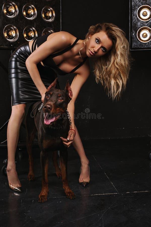 秀丽和方式 有华美的卷发的妇女拥抱短毛猎犬 黑暗的背景,与狗的女孩隔壁 免版税图库摄影
