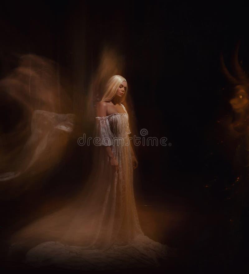 秀丽和黑暗的妖怪 Ariadne和Minotaur 女孩是白肤金发的,象一个鬼魂,在一件白色葡萄酒礼服 库存照片