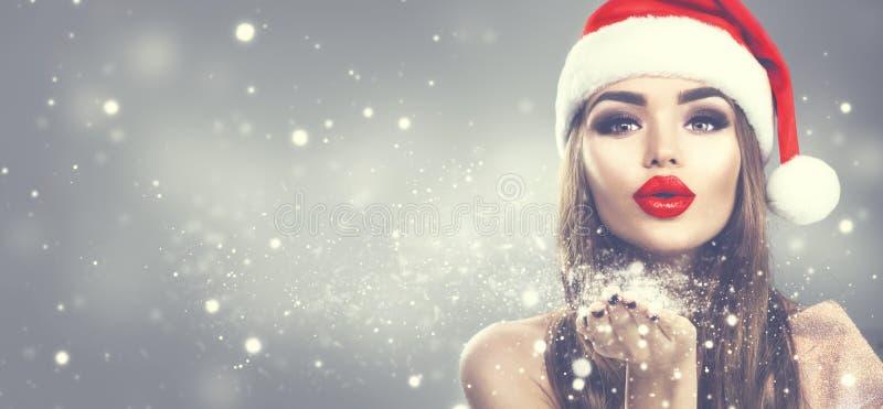 秀丽圣诞老人的帽子吹的雪的模型妇女在她的手上 圣诞节冬天在度假被弄脏的冬天背景的时尚女孩 免版税图库摄影