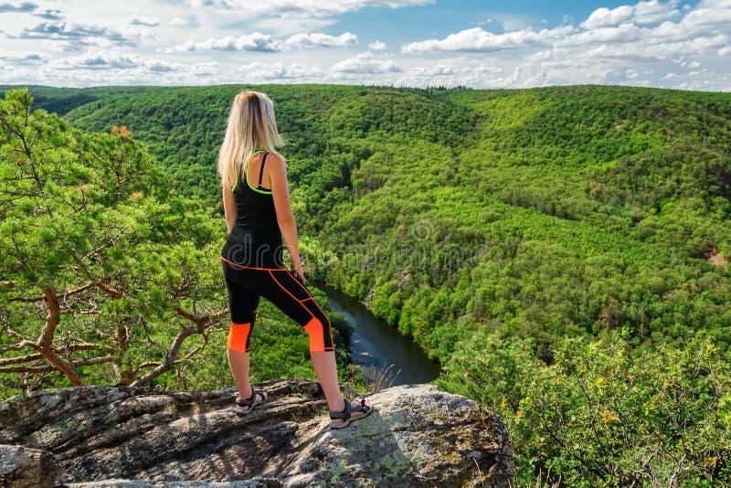 秀丽在岩石的年轻女人立场从后面 室外,健身概念 河Dyje,国立公园Podyji,捷克共和国 库存照片