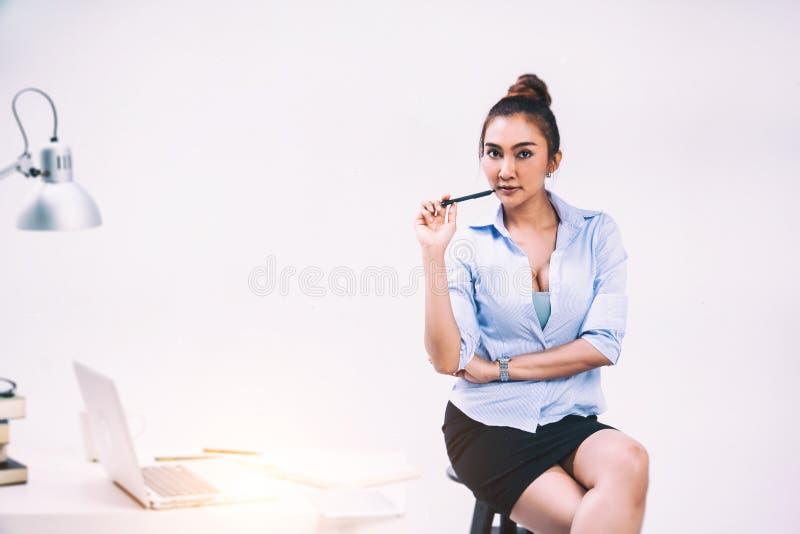秀丽夫人的抽象派设计背景有蓝色衬衣和黑礼服的在手中是举行笔 坐黑椅子 免版税库存图片