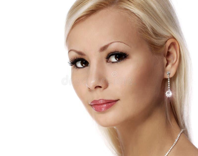 秀丽女孩。美丽的面孔。有被隔绝的金刚石首饰的魅力白肤金发的妇女 免版税库存照片