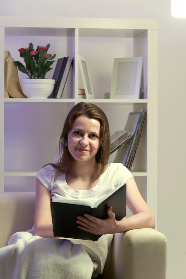 秀丽女孩在家读了书 免版税库存图片