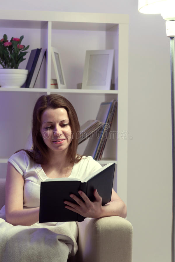 秀丽女孩在家读了书 免版税图库摄影