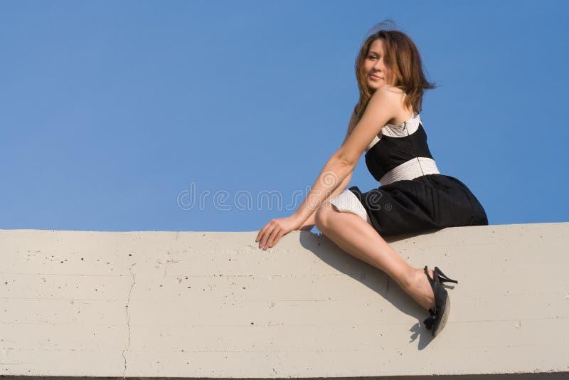 秀丽女孩坐墙壁 库存照片