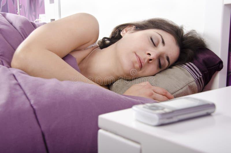 睡觉的女孩近到电话 免版税库存照片