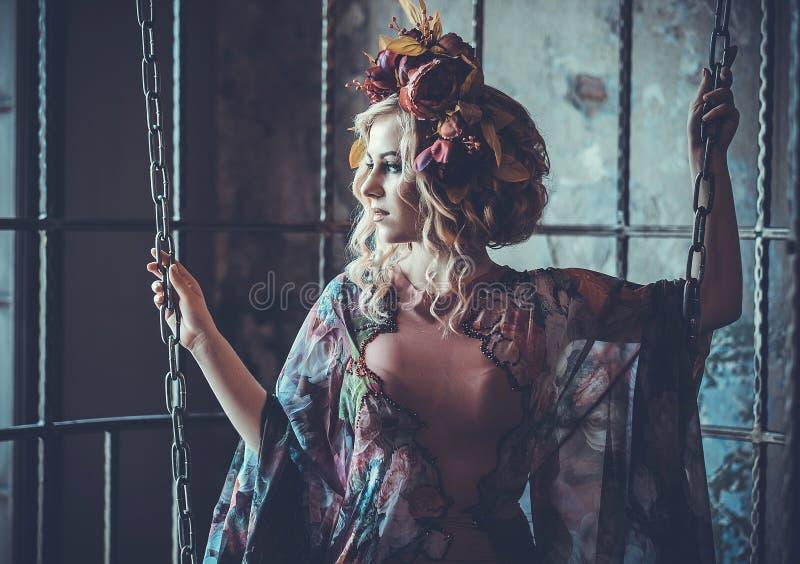 秀丽妇女在宫殿 豪华笼子的时尚时髦的女孩 花礼服和花花圈  免版税库存照片