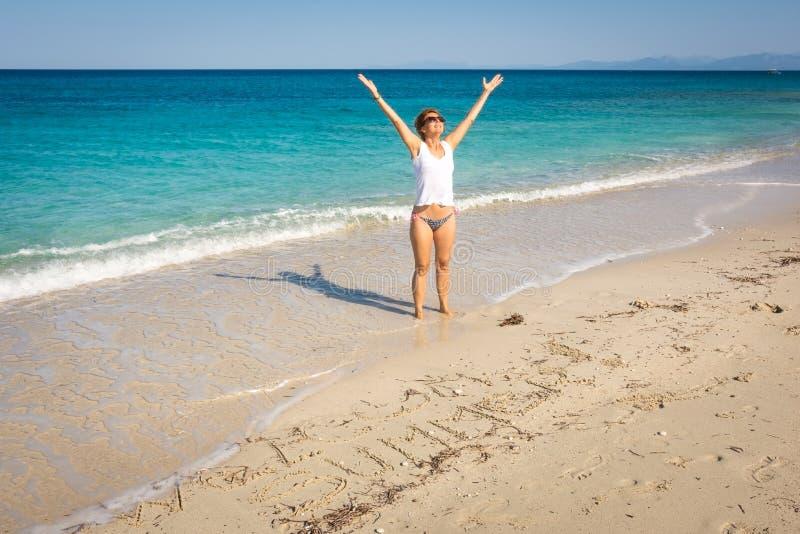 秀丽妇女在希腊激发海边海滩 免版税库存照片