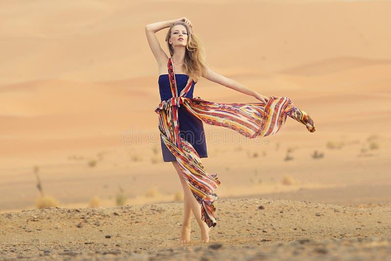 秀丽妇女的画象一件礼服的在热的沙漠 免版税库存图片