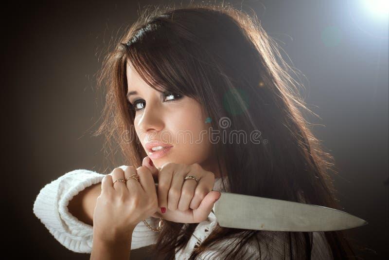 秀丽妇女画象拔出她的刀子 攻击准备好 免版税库存照片