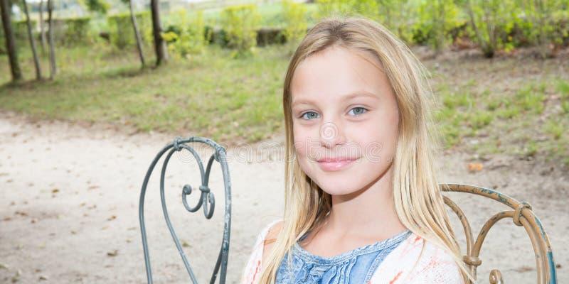 秀丽少年女孩对照相机微笑着坐长凳 免版税库存图片