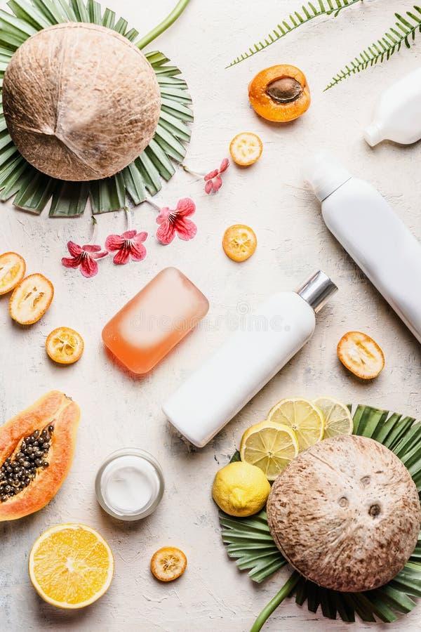 秀丽平的被放置的背景用椰子和热带水果和化妆品有嘲笑的:瓶,肥皂,润肤液 ?? 免版税库存照片