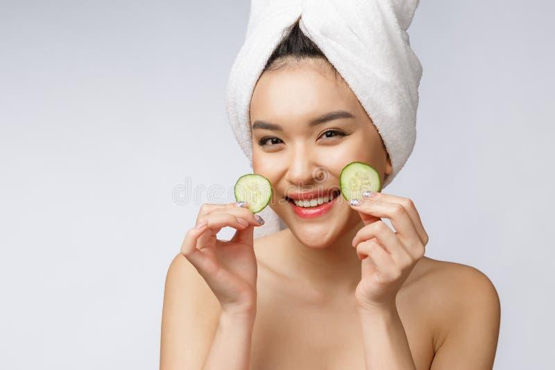 秀丽年轻亚洲妇女皮肤护理图象用在白色背景演播室的黄瓜 库存图片