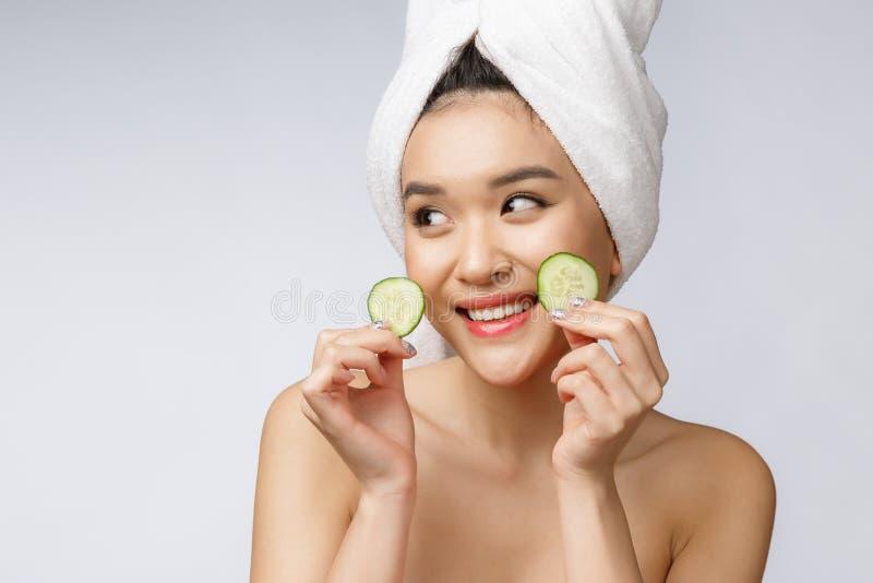 秀丽年轻亚洲妇女皮肤护理图象用在白色背景演播室的黄瓜 库存照片