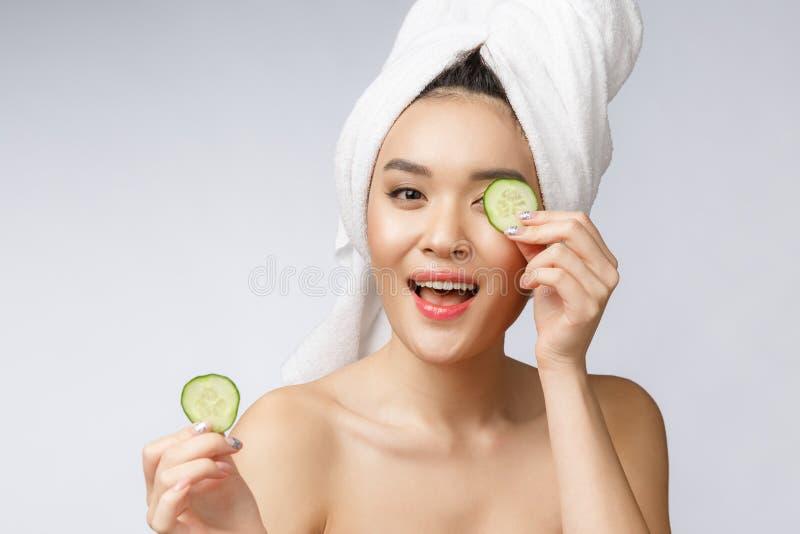 秀丽年轻亚洲妇女皮肤护理图象用在白色背景演播室的黄瓜 免版税库存图片