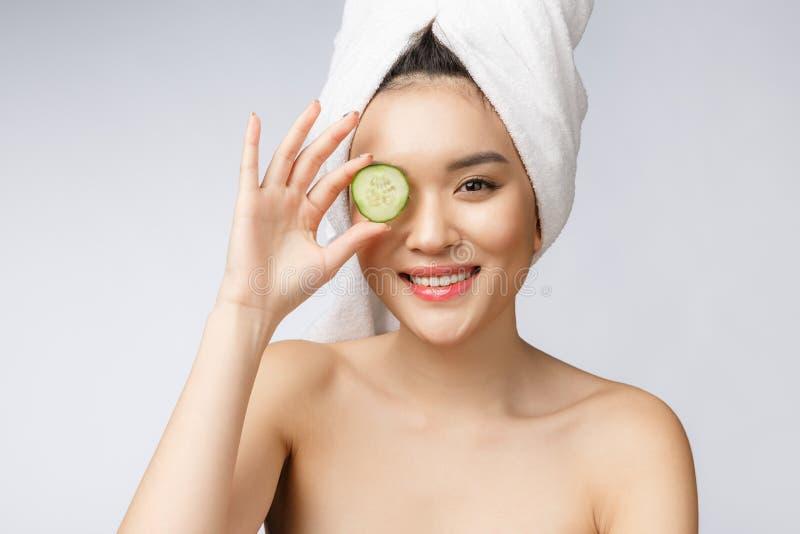秀丽年轻亚洲妇女皮肤护理图象用在白色背景演播室的黄瓜 免版税库存照片
