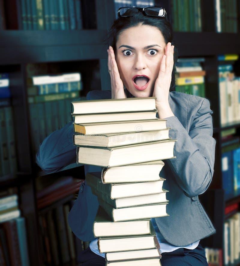 秀丽年轻女人看书照片画象在图书馆,拿着许多书,生活方式人概念的学生里 图库摄影