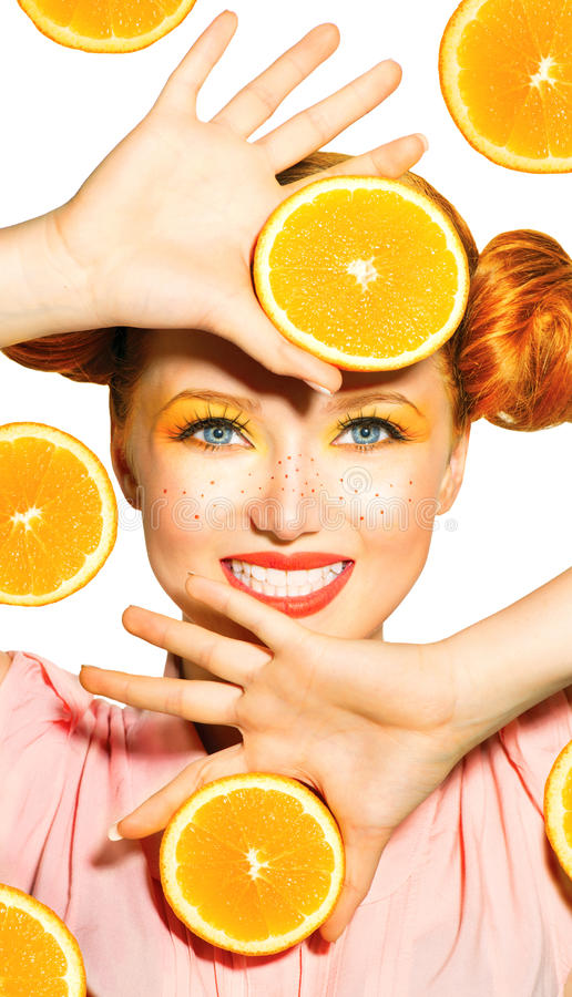 秀丽式样女孩采取水多的桔子 免版税库存图片
