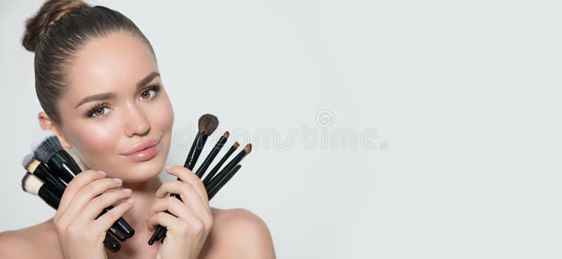 秀丽式样女孩,化妆师藏品套组成刷子和微笑 有完善的皮肤的美丽的深色的少妇和 库存图片