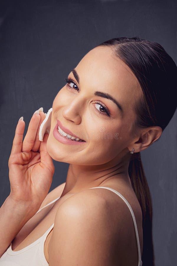 秀丽护肤 取消面孔构成的微笑的妇女使用化装棉 免版税库存图片