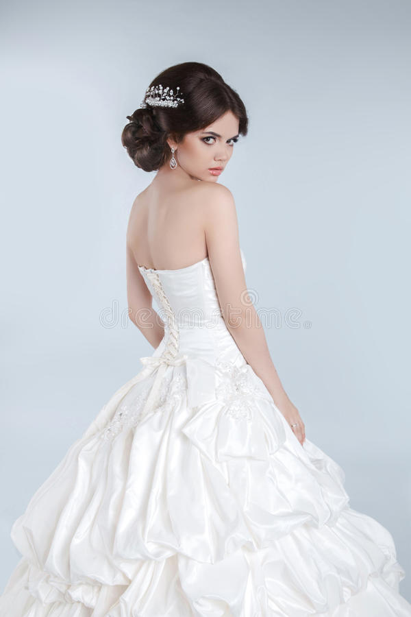 秀丽时尚年轻新娘式样摆在与ha的婚礼礼服 免版税库存照片