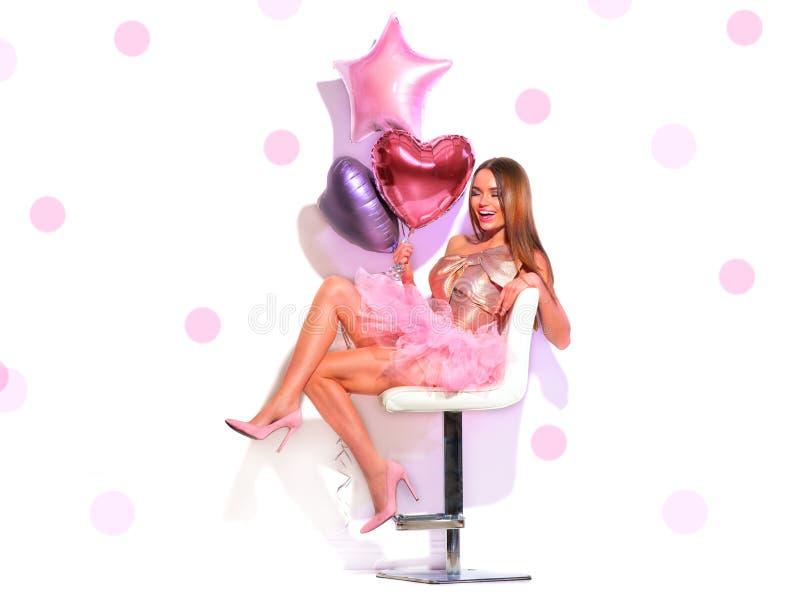 秀丽时装模特儿有获得心形的气球的女招待乐趣,坐椅子 美丽的新深色的妇女 免版税库存图片