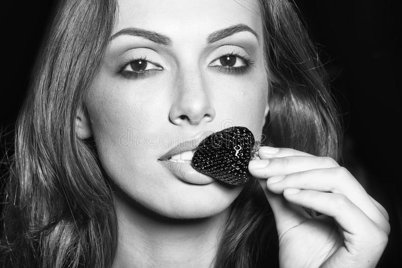 秀丽时装模特儿画象 吃红色草莓的性感的妇女 免版税库存照片