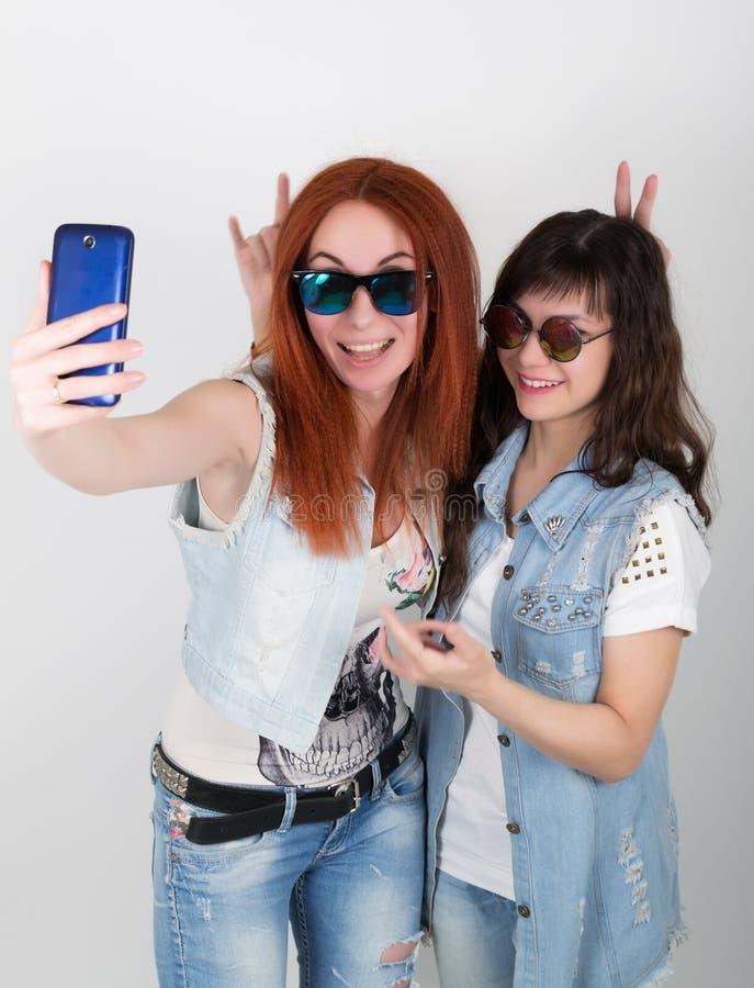 秀丽有的行家女孩耳机,在电话做selfie 少年鬼脸 免版税库存图片